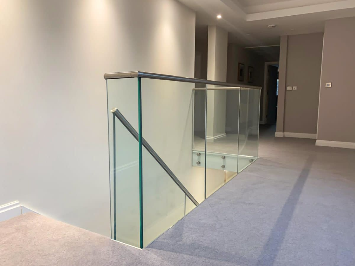 Frameless glass standoff button system on landing with stainless steel slotted handrail