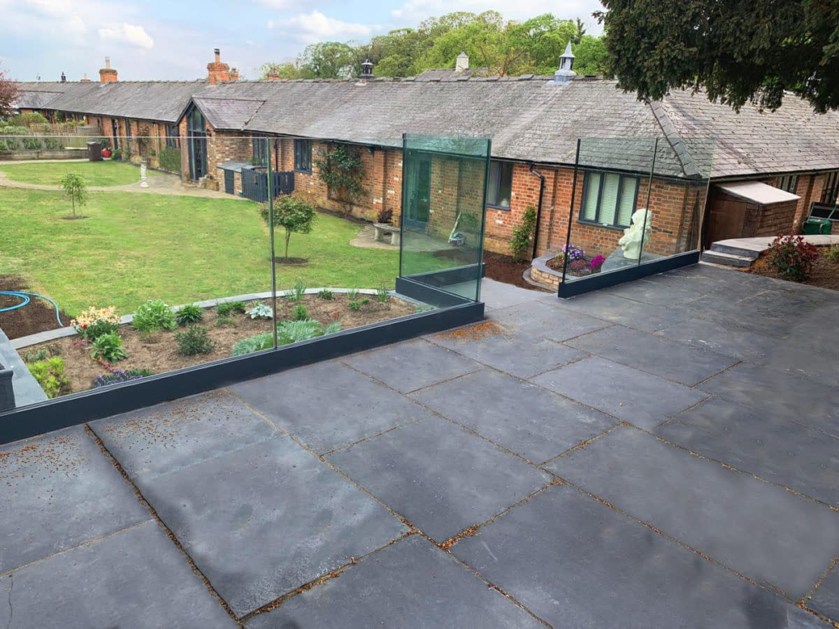 Anthracite Grey Frameless Channel System Installed on Raised Patio Overlooking a Garden